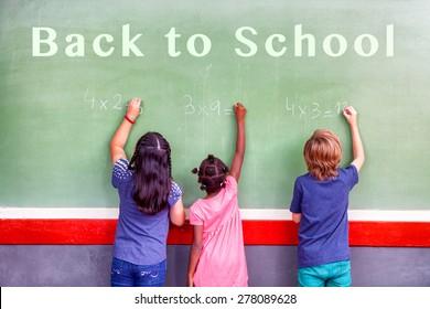 Back to school concept. Multi ethnic classroom writing on chalkboard.