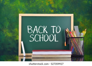 Back to School concept. Notebook and stationery in front of chalkboard on dark green background