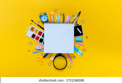 Back to school concept notepad, pencil case, stationery and school supplies. Top horizontal view copyspace yellow abstract background