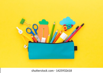 Back to school concept. Pencil case with school stationery on a yellow background.