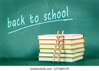 back to school concept with pencil ladder on stack of books against green chalkboard