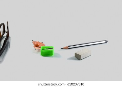 Back to school concept- a Pencil,erasor, sharpner an cut slice of the pencil on white table with or without spectacles not properly aranged isolated.
