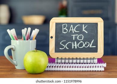Back to school. Concept with pens, books, an apple and blackboard with inscription : Back to school
