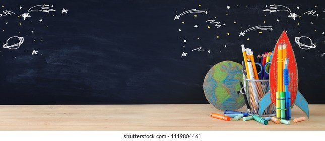 Back to school concept. rocket, earth globe and pencils in front of classroom blackboard