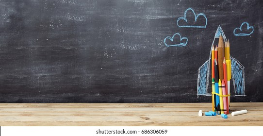 Back to school concept with rocket made from pencils over chalkboard background