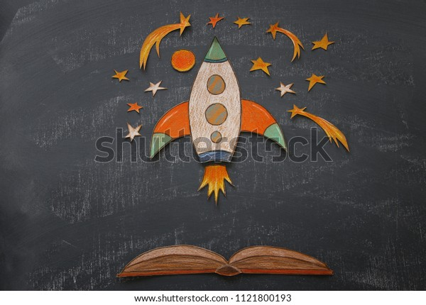 Back to school concept. rocket with pencils, space elements shapes cut from paper and painted over classroom blackboard background