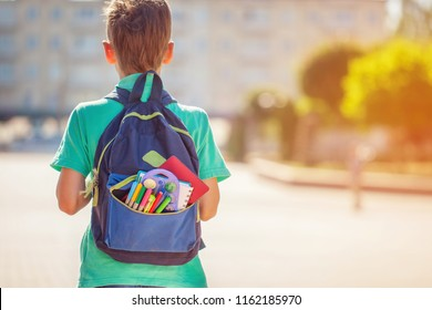 Back to school concept. Schoolboy with full backpack go to school. Back view.