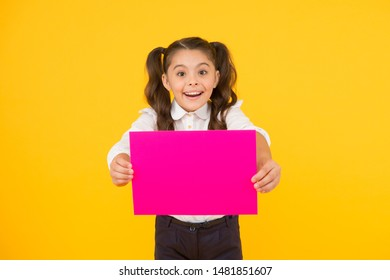 Back to school concept. Schoolgirl pupil show poster. Schoolgirl hold poster copy space. News information promotion. Upcoming event. Look here. Girl school uniform hold poster. Changes coming.