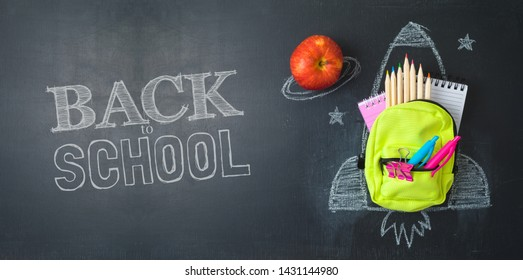 Back to school concept with small bag backpack, school supplies and rocket sketch over chalkboard background. Top view from above