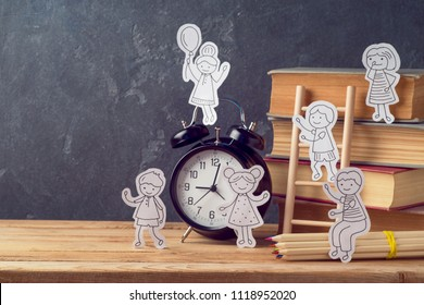 Back to school concept with small children doodles and old books over table background