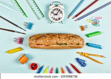 Back to school concept. school snack sandwich and school supplies on blue background. Flat lay stylish set top view. copy space.