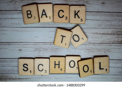 Back to School concept. Back to school spelled out on scrabble letters on a rustic wooden background. Preparation for going back to school after the summer holidays.