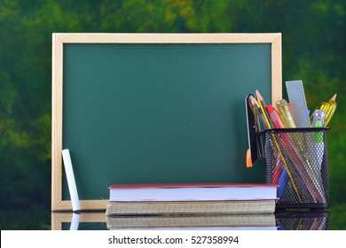 Back to School concept with stationery on table in front of chalkboard