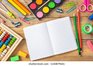 Back to school concept. School supplies and blank notebook on wooden background, space for text, top view