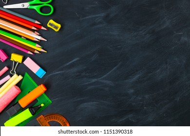 Back To School concept. School supplies on blackboard background, accessories for the schoolroom - pencils, scissors, chalk, markers. Сopy space top view