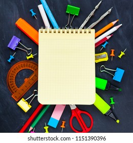Back To School concept. School supplies on blackboard background, accessories for the schoolroom - pencils, notebooks, scissors, chalk, markers.  Сopy space top view