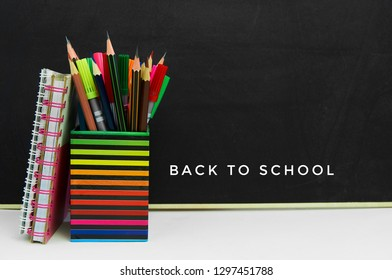 Back to school concept with school supplies on blackboard background with copy space