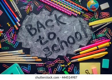 Back to school concept. School supplies on blackboard background. Back to school concept with stationery. Schoolchild and student studies accessories. Top view.