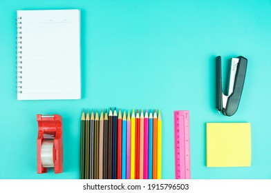 Back to school concept with school supplies, paper,crayons on green background with copy space
