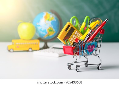 Back to school concept. School supplies, schoolbus and shopping cart with stuff