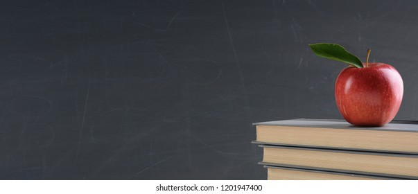Back to school concept: Text books with a red apple in front of a blank chalk board. Banner sized image with copy space.