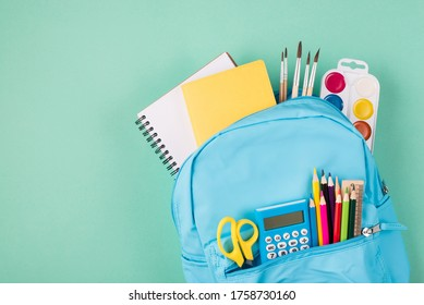 Back to school concept. Top above overhead view photo of full blue backpack filled with school stationery isolated on turquoise background