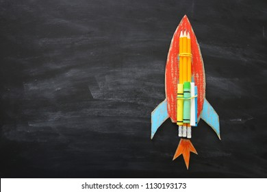 Back to school concept. Top view image of handmade cardboard rocket and clouds with pencils over classroom blackboard background.