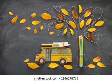Back to school concept. Top view image of school bus and pencils next to tree sketch with autumn dry leaves over classroom blackboard background