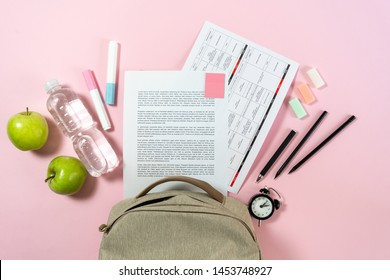 Back to school concept. Top view of backpack, green apples paper blanks and colorful stationery on pastel pink background