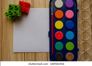 back to school concept watercolor palet flat lay with blank paper and building blocks.