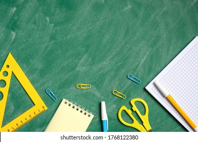 Back to school concept. Yellow school stationery on green chalkboard. Flat lay ruler, paper note, pen, scissors, notebook. View from above