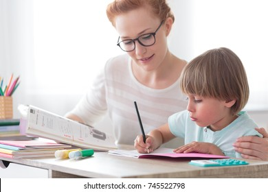 Back to school concept, young mother sitting at desk helping her little son with homework