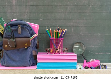 Back to school concept.Books, textbooks, backpack and stationery supplies on blackboard.