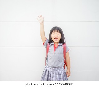 Back to School Concept.Happy Funny little asian girl raising hands and very excited and glad when she go back to school.Child from elementary school kindergarten with japan bag.Education.