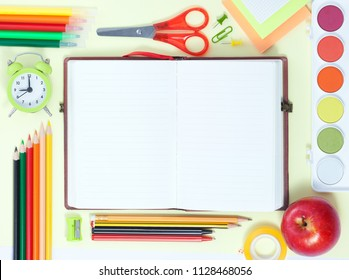 Back to School Conceptl: Empty Notebook, Colorful Pens, Pencils, Felt Pens, Red Apple, Sissors, Palette of Paint on the Yellow Background