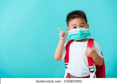 Zurück zur Schule Coronavirus Covid-19 Bildung. Portrait Asiatischer, süßer kleiner Kinderkindjunge Kindergarten trägt Gesichtsmaske-Schutz und Schultasche mit Finger nach Seite, Studioaufnahme einzeln auf blauem Hintergrund