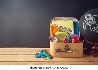 Back to school creative background with cardboard suitcase and school supplies on wooden table. Sale concept