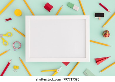 Back to school. School creative desk. Blank frame top view and stationery ruller, pen, paper plane, scissors. Flat lay.