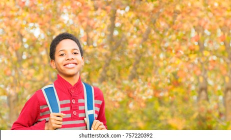 Back to School. Cute African-American Boy going to or from school wearing a backpack. Room for copy or text over Fall trees in background .
