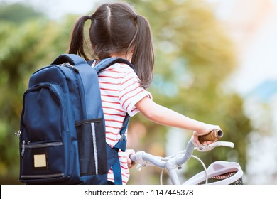 493b0fe23d29 Cute asian child girl with backpack biking a bicycle and going to