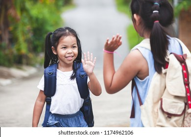 Back to school. Cute asian child girl with school bag and her elder sister making hi five gesture before go to school with fun