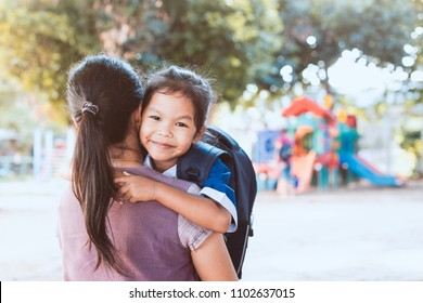 Back to school. Cute asian pupil girl with backpack hugging her mother in the playground before go to classroom in the school.
