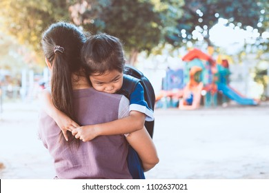 Back to school. Cute asian pupil girl with backpack hugging her mother with sadness in the playground before go to classroom in the school.