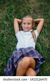 Back to school. Cute girl from elementary school lying at grass