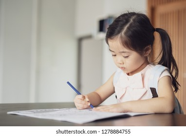 Back to school, Cute little girl painting a picture in home, Girl writing in notebook with pencil at her bedroom.