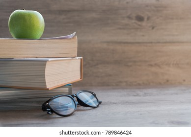 Back to school education and bookworm knowledge concept. Stack of books with apple fruit and glasses on wooden table background in classroom or library with copy space.