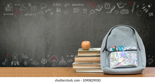 Back to school, education concept with books, textbooks, backpack and stationery supplies on classroom desk with teacher's chalkboard background with educational doodle for new academic year begin