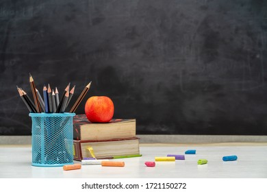 Back to school and education concept. Books with pencil holder on white table. blackboard in background.