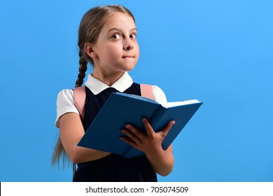 Back to school and education concept. Girl holds big open blue book. School girl with surprised face thinking of some idea isolated on blue background. Pupil in school uniform with braids and backpack