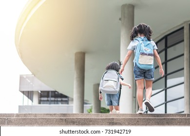 Back to school education concept with girl kids (elementary students) carrying backpacks going, running to class on school first day and walking up building stair happily
